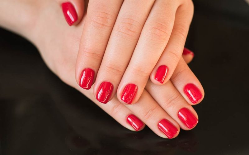 red-manicure-with-nail-on-a-black-background-pf7v4vz